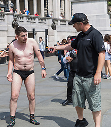 Two men, thought to be street performers who fancied an illegal dip in the cool waters of Trafalgar Square's fountains have their plans curtailed as a man wearing a black Greater London Authority and carrying a radio but displaying no proper identification, tackles one of them, slamming him into the ground. London, August 02 2019.