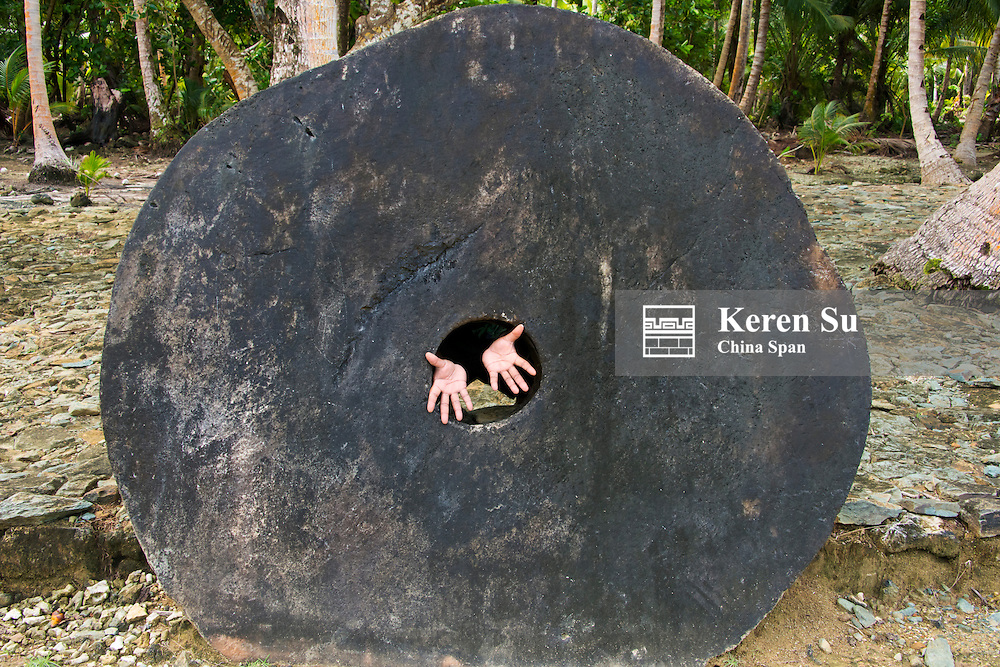 Stone money (Rai stones) in the bank, hands extending from the hole in the disc, Yap Island, Federated States of Micronesia