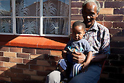 "21 February 2010, Sharpeville, South Africa. Simon ""Bull"" Lehoko, voted one of the top 50 football players of all time, with his grandson at his home in Sharpeville."