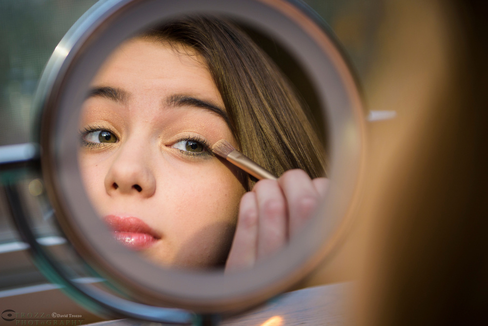 Teenager age 13-16 applies make-up and looks at her reflection in a mirror.