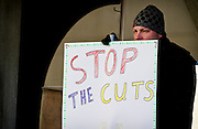 """MADISON, WI — FEBRUARY 13, 2015: Jesse Ransom holds a protest sign and looks on during the """"Stop the Cuts"""" Rally on Library Mall, Saturday, February 14, 2015. The rally drew hundreds of student, faculty and community supporters in spite of the cold Midwest weather."""