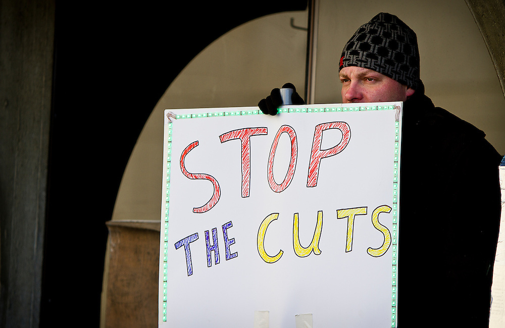 "MADISON, WI — FEBRUARY 13, 2015: Jesse Ransom holds a protest sign and looks on during the ""Stop the Cuts"" Rally on Library Mall, Saturday, February 14, 2015. The rally drew hundreds of student, faculty and community supporters in spite of the cold Midwest weather."