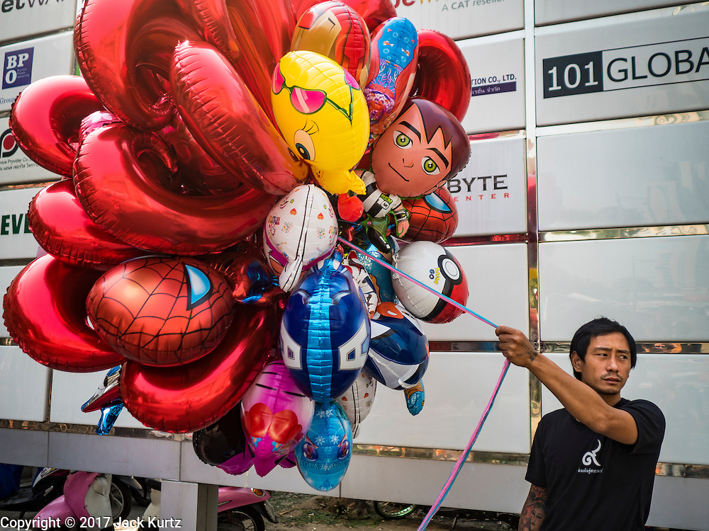"14 FEBRUARY 2017 - BANGKOK, THAILAND:  A vendor selling inflatable toys waits for customers during a mass wedding in the Bang Rak district in Bangkok. Bang Rak is a popular neighborhood for weddings in Bangkok because it translates as ""Village of Love."" (Bang translates as village, Rak translates as love.) Hundreds of couples get married in the district on Valentine's Day, which, despite its Catholic origins, is widely celebrated in Thailand.     PHOTO BY JACK KURTZ"