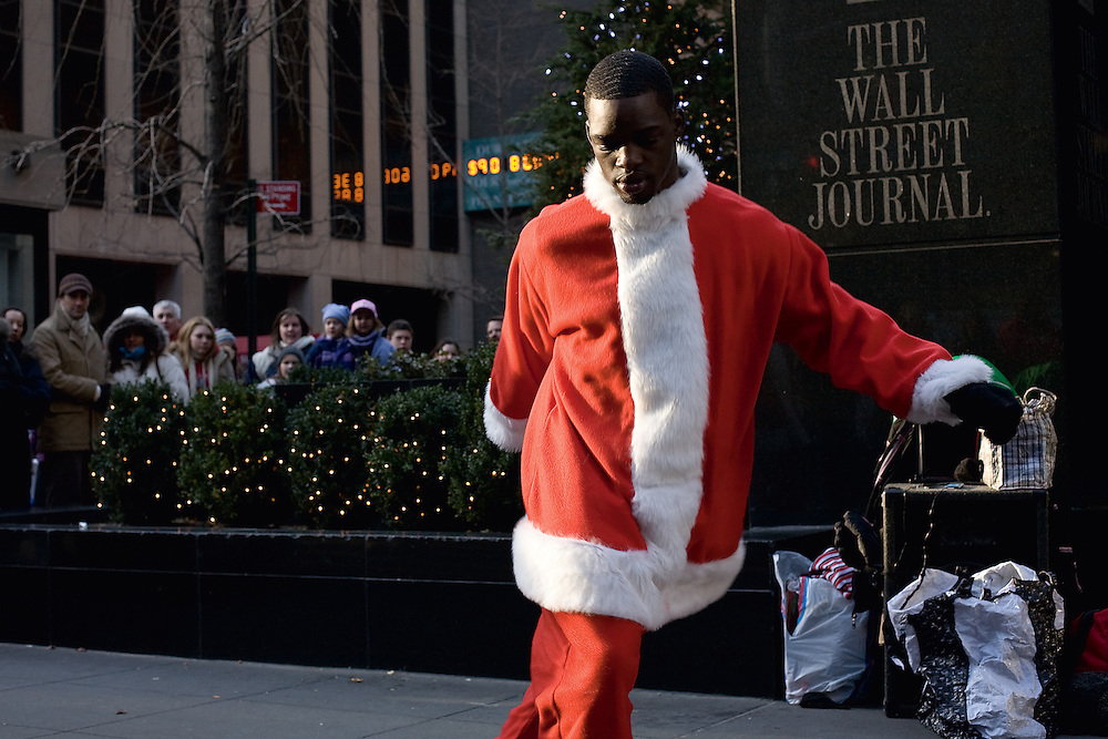 A street performer in a Santa Claus costume in the middle of a dance in front of the Wall Street Journal offices on the Avenue of the Americas.