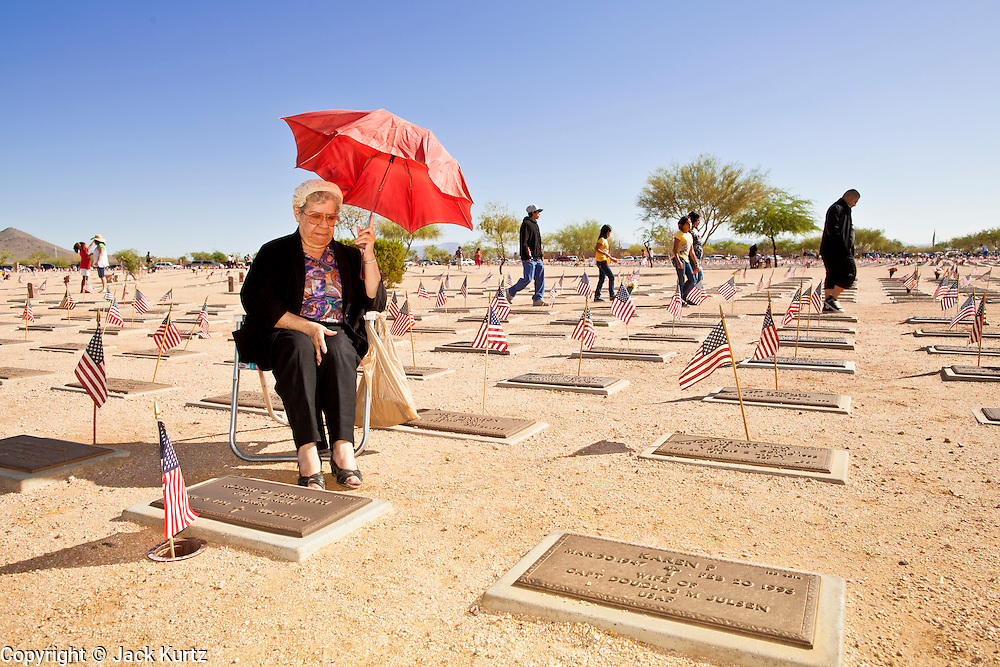 30 MAY 2011 - PHOENIX, AZ: MARIA BEILSMITH at the grave site of her late husband, a US Army veteran who fought in the Korean War, as people walk through the cemetery during Memorial Day services in the National Memorial Cemetery in Phoenix, AZ, Monday. Memorial Day was celebrated with services across the United States Monday.    Photo by Jack Kurtz