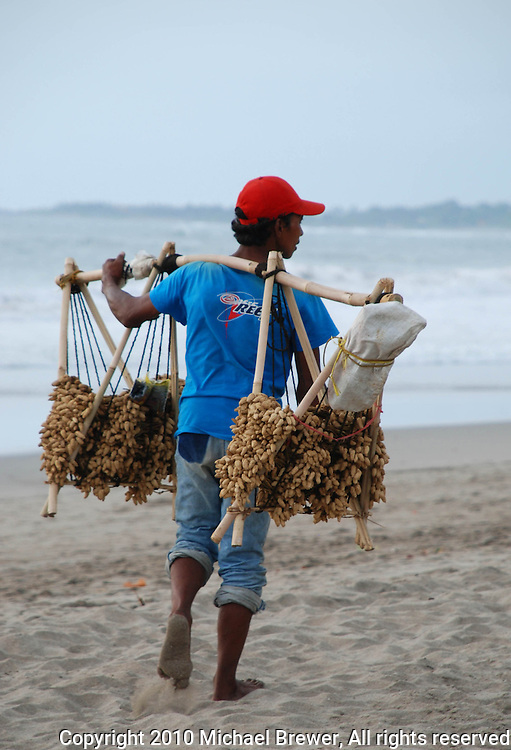 A peanut salesman with his wares walking along the beach in Bali, Indonesia.
