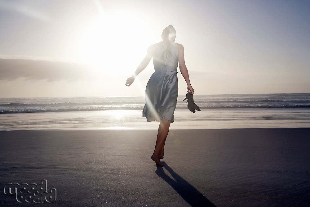 Woman running on beach  against sunset low angle view back view