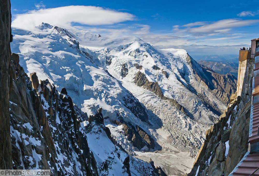 """Dôme du Goûter (center 14,121 feet or 4304 meters) is a shoulder of massive Mont Blanc (in clouds on left at 15,782 feet elevation). Massive glaciers fill the view from Aiguille du Midi, Chamonix, France, Europe..  Panorama stitched from 3 overlapping images. One of 17 photos published in Ryder-Walker Alpine Adventures """"Inn to Inn Alpine Hiking Adventures"""" Catalog 2006."""