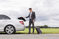 Full length of young businessman unloading luggage from broken down car at countryside