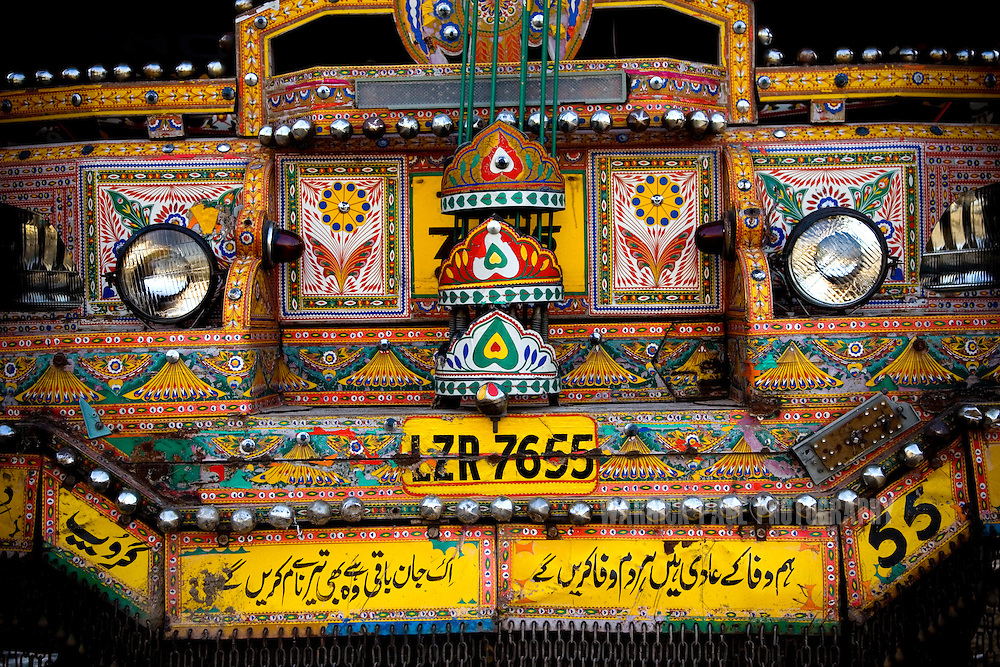 RAWALPINDI, PAKISTAN - OCTOBER 9: Urdu poetry adorns the front of a garishly painted truck at a painting and repair yard, October 9, 2008, in Rawalpindi, Pakistan. The heavily adorned Bedford trucks have become a national icon and cost upwards of one million rupees (USD$12,500) for a full makeover. Much of the artwork consists of a cultural mix of religious and secular, Pakistani film and music stars, cricket legends, romanticized military imagery of F-16 fighter jets and Ghauri missiles, the Prophet's winged horse, Buraq, and dreamlike scenes of wooded lakes and snow-capped mountains and exotic animals. (Photo by Warrick Page)