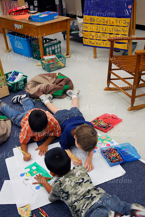 Kindergarten classroom students working together on lesson sitting at tables or on the floor in Middleton-Burney Elementary Crescent City FL.