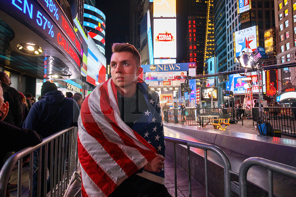 © Licensed to London News Pictures. 09/11/2016. New York CIty, USA. A man wearing an American flag reacts to news that Donald Trump is elected as the next president of the United States, while gathering in Times Square, New York City, on Wednesday, 9 November. Photo credit: Tolga Akmen/LNP