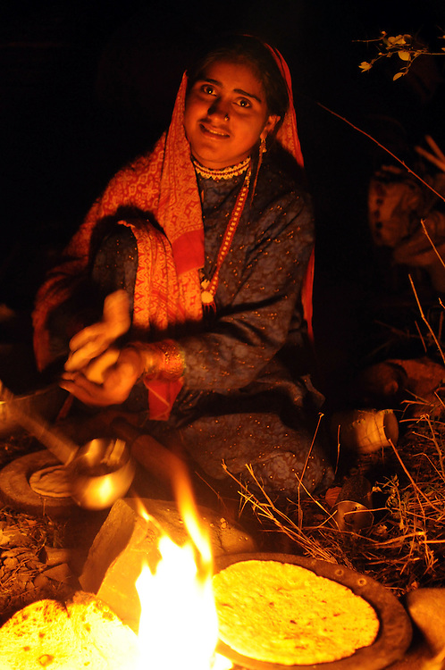 "Apa makes chapatis over fire before breaking camp one ""morning"". (This was rare - usually no food was made before the day's journey, only tea. Food was generally cooked only after arriving at the next camp."