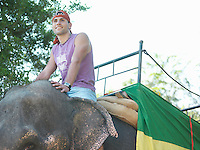 Portrait of young man riding elephant smiling trees in background