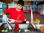 "26 JUNE 2020 - DES MOINES, IOWA: ETHAN KEOMALA makes deep fried Oreos at Fair Food Friday in Des Moines. The 2020 Iowa State Fair, like many state fairs in the Midwest, has been cancelled this year because of the COVID-19 (Coronavirus) pandemic. The cancellation of the fair left many small vendors stranded with no income. Some of the fair food vendors in Iowa started ""Fair Food Fridays"" on a property a few miles south of the State Fairgrounds. People drive up and don't leave their cars while vendors bring them the usual midway fare; corndogs, fried tenderloin sandwiches, turkey legs, deep fried Oreos, lemonaide and smoothies. Fair Food Friday has been very successful. The vendors serve 450-500 people per Friday and during the lunch rush people wait in line in their cars 30 - 45 minutes to place an order.     PHOTO BY JACK KURTZ"