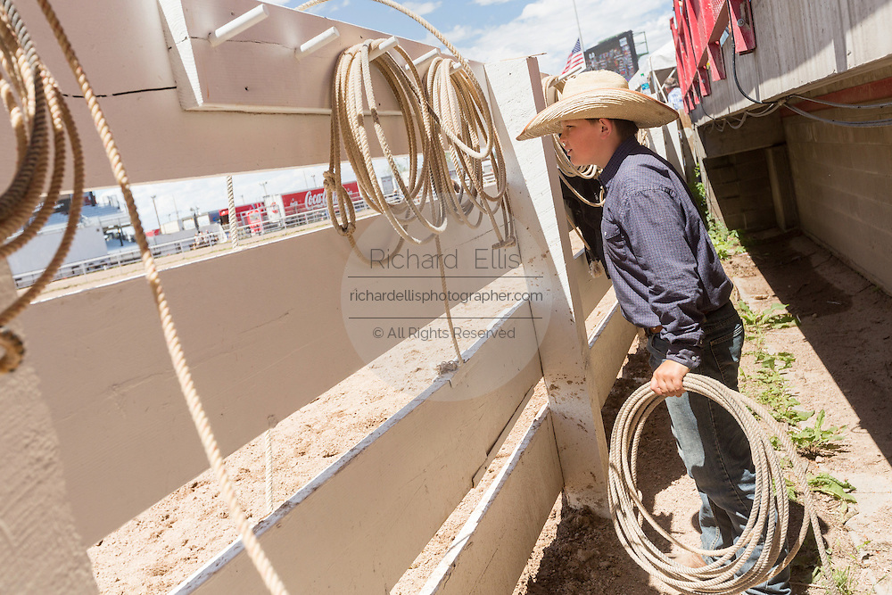 A young cowboy watches the rodeo during the Cheyenne Frontier Days July 25, 2015 in Cheyenne, Wyoming. Frontier Days celebrates the cowboy traditions of the west with a rodeo, parade and fair.