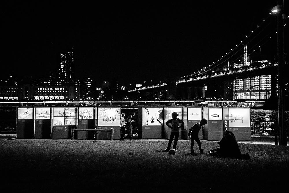A family enjoys a night at Brooklyn Bridge Park.