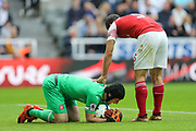 Petr Cech (#1) of Arsenal reacts in pain after snatching the ball away from the boot of Yoshinori Muto (#13) of Newcastle United during the Premier League match between Newcastle United and Arsenal at St. James's Park, Newcastle, England on 15 September 2018.
