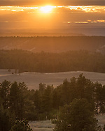 The departing sun casts a golden glow on the forests and grasslands in the Custer National Forest. This view is from Poker Jim Butte.