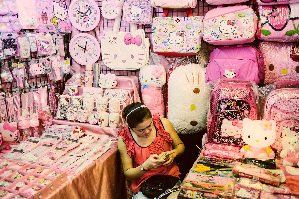Woman selling Hello Kitty bags and accessories at a night market in Bangkok.
