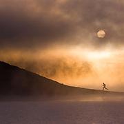A photo of a man running along the shore of a foggy lake at dawn near Truckee California