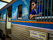 31 MAY 2017 - CHACHOENGSAO, THAILAND:  A passenger looks out the window of a Bangkok bound train at the train station in Chachoengsao, a provincial town about 50 miles and about an hour by train from Bangkok. The train from Chachoengsao to Bangkok takes a little over an hour but traffic on the roads is so bad that the same drive can take two to three hours. Thousands of Thais live outside of Bangkok and commute into the city for work on trains, busses and boats.      PHOTO BY JACK KURTZ