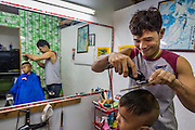 20 JUNE 2014 - SAMUT SAKHON, SAMUT SAKHON, THAILAND: A Burmese barber gives a boy haircut in a Burmese barbershop in Samut Sakhon. Hundreds of thousands of migrant workers from Myanmar work in the Thai fishing industry. Samut Sakhon, (sometimes still called Mahachai, its historical name) is a large fishing port. Many Burmese live in the town and work in the fish process plants. Although hundreds of thousands of Cambodians fled Thailand last week after the military coup, the Burmese workers have stayed and are still working in many Thai towns.    PHOTO BY JACK KURTZ