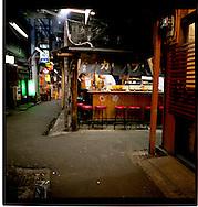 Man has late dinner of noodles in katsuo dashi (bonito broth) at open air restaurant, Shinjuku, Tokyo, Japan.