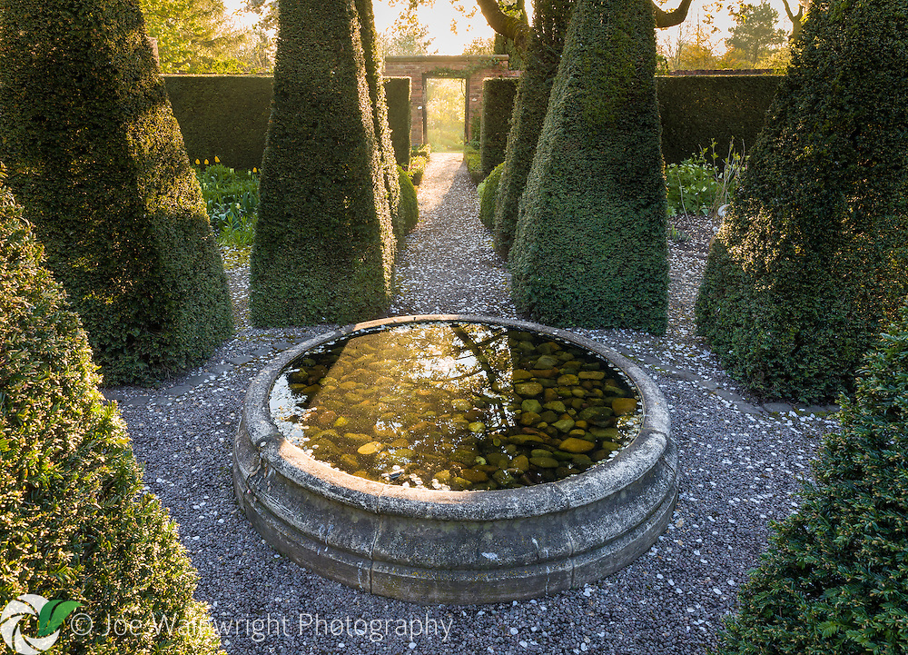 Dawn light shines through a gateway into The Well Garden at Wollerton Old Hall Garden, Shropshire - photographed in April