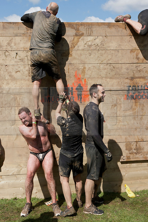 © Licensed to London News Pictures. 12/05/2012. Kettering, UK. Tough Mudder competitors work together to climb over military style high walls. Thousands of people took part in Tough Mudder today (12/05) in the grounds of Boughton House, Northamptonshire. The 12 mile course which was designed by British special forces soldiers, consisted of 25 extreme obstacles including water, mud, electrocution, and high walls. The challenge is designed to test teamwork abilities as well as physical strength and stamina . Photo credit : James Gourley/LNP