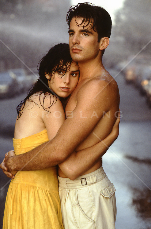 shirtless man embracing a woman on the streets of New York City in the rain