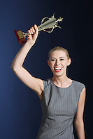 Woman hoisting trophy over head against dark background