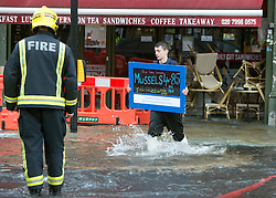 © Licensed to London News Pictures. 06/10/2014. Twickenham, UK. A fishmonger retrieves a sign that had floated away from the shop he works at.  Firefighters help to contain a mains water pipe which has burst in King Street Twickenham today 6th October 2014. It appears that workmen working in the area have used a JCB digger to stem the flow. Many local shops and businesses have been flooded.   Photo credit : Stephen Simpson/LNP