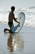 Surfer Checking waves and waxing board. Samurai Beach Port Stephens, NSW, East Coast Australia