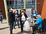 22 APRIL 2020 - DES MOINES, IOWA: SUSAN AYALA carries a bag of grab and go meals to people waiting in a car at Edmunds Elementary School. Schools in Iowa are closed for the rest of the school year because of the COVID-19 (Coronavirus/SAR-CoV-2) pandemic. Des Moines Public Schools expanded their school lunch and distance learning efforts this week. Lunches are being distributed at all of the district's elementary and middle schools and officials have started distributing computers so students can participate in distance learning. The meal distribution was done according to social distancing guidelines.           PHOTO BY JACK KURTZ