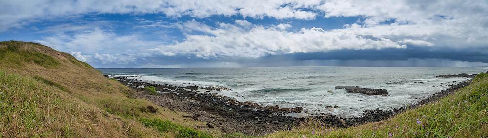 A tropical rainshower approaches this rocky point near Kealia Beach.