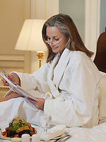 Woman wearing bathrobe reading sitting on bed