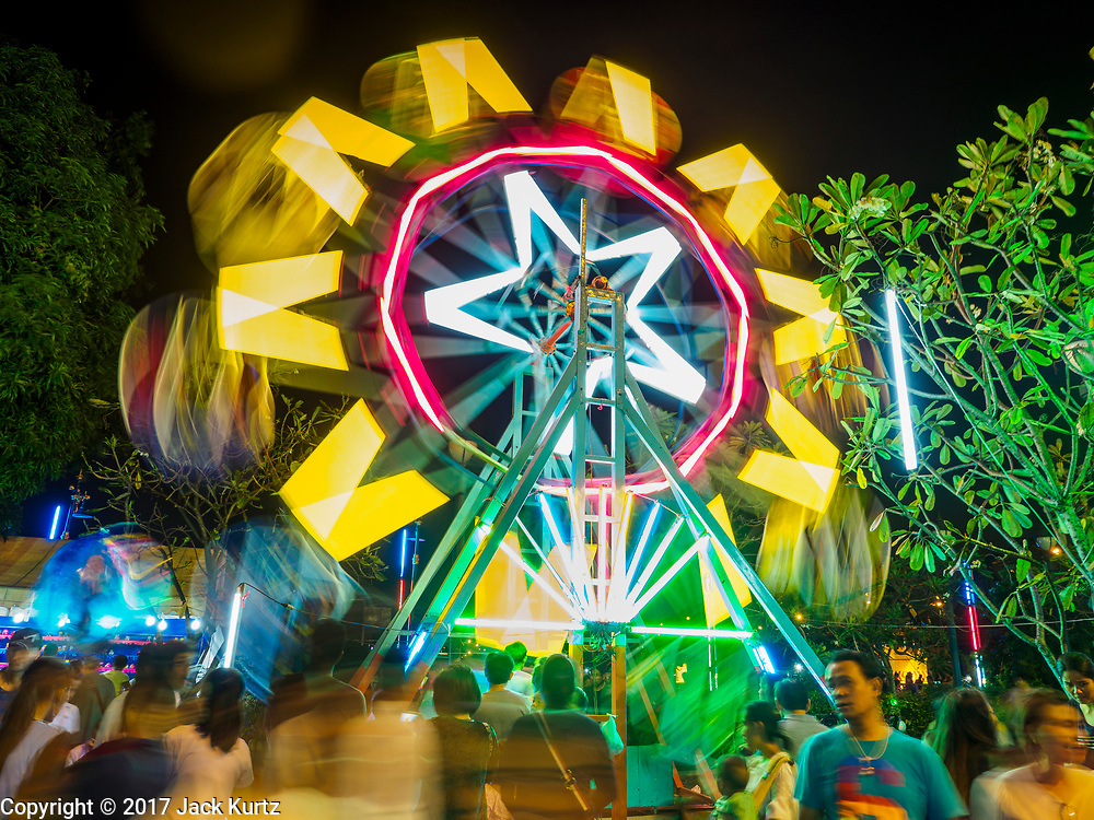 "03 NOVEMBER 2017 - BANGKOK, THAILAND: A Ferris Wheel entertains children during Loi Krathong at Wat Prayurawongsawat on the Thonburi side of the Chao Phraya River. Loi Krathong is translated as ""to float (Loi) a basket (Krathong)"", and comes from the tradition of making krathong or buoyant, decorated baskets, which are then floated on a river to make merit. On the night of the full moon of the 12th lunar month (usually November), Thais launch their krathong on a river, canal or a pond, making a wish as they do so. Loi Krathong is also celebrated in other Theravada Buddhist countries like Myanmar, where it is called the Tazaungdaing Festival, and Cambodia, where it is called Bon Om Tuk.     PHOTO BY JACK KURTZ"
