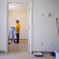 Sergio Zarate looks over a nearly-finished bedroom during a refurbishing operation at Battered Families Services in Gallup Saturday.