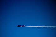 Passenger jet aircraft viewed from porthole of another in flight on route to America