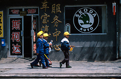 CHINA BEIJING APR99 - Three Chinese schoolchildren walk past a hardware store displaying a large Skoda Auto logo. In recent years, lots of western automobile manufacturers have invested in joint-venture projects, enabling to them to manufacture and sell cars for the Chinese market. ..jre/Photo by Jiri Rezac..© Jiri Rezac 1999..Contact: +44 (0) 7050 110 417.Mobile:  +44 (0) 7801 337 683.Office:  +44 (0) 20 8968 9635..Email:   jiri@jirirezac.com.Web:    www.jirirezac.com..© All images Jiri Rezac 1999 - All rights reserved.