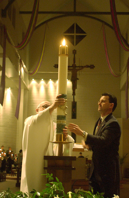 Fr. Steven Amann, pastor of St. Elizabeth Ann Seton Parish in New Berlin, places the Easter candle in its stand following the candle's lighting to open the Easter Vigil. (Photo by Sam Lucero)