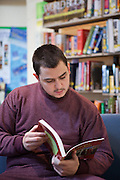 A prisoner reads a text book in the prison library. HMP The Mount, Bovingdon, Hertfordshire