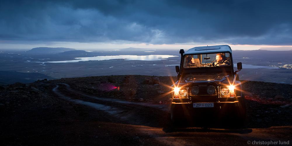 Félagar í Land Rover í ljósaskiptunum á Miðdalsfjalli. Apavatn, Mosfell, Vörðufell og Hestfjall í baksýn. Mates on their Land Rover in twilight on Mount Middalsfjall. Lake Apavatn and Mountains Mosfell, Vordufell and Hestfjall in background.