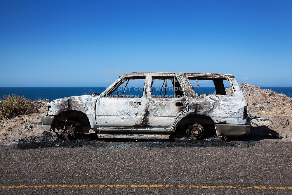 Image of a burned out car roadside in Baja with the Sea of Cortez in the background, Baja California Sur, Mexico