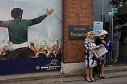 Women infront of a a jocket poster during the annual Royal Ascot horseracing festival in Berkshire, England. Royal Ascot is one of Europe's most famous race meetings, and dates back to 1711. Queen Elizabeth and various members of the British Royal Family attend. Held every June, it's one of the main dates on the English sporting calendar and summer social season. Over 300,000 people make the annual visit to Berkshire during Royal Ascot week, making this Europe's best-attended race meeting with over £3m prize money to be won.
