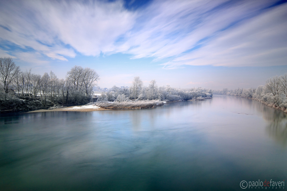 A winter view of the Po River, the largest and longest river in Italy, as it looks like from a road bridge near Carignano in Piedmont, Italy. The whites of the frost-covered trees nicely contrast with the deep emerald green of the water.