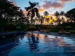 Fiji, Taveuni Island. Sunset and silhouetted palm trees over a swimming pool.