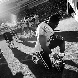 University of Virginia player, Clint Sintim (middle, #94) drops to a knee and prays as the final seconds of the fourth quarter of the last game of the year run off the clock during the game against Virginia Tech at Lane Stadium in Blacksburg, Virginia on Saturday. Virginia lost 0-17 to Virginia Tech.
