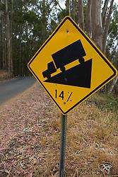 A yellow road sign warns trucks of a 14% grade down a hill,  Mendocino, California, USA.